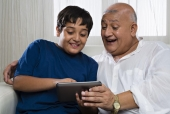 Boy and his grandfather smiling while using a digital tablet