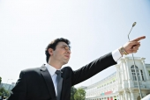 Close-up of a businessman  pointing towards sky, Connaught Place, New Delhi, India