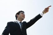 Close-up of a businessman  pointing towards sky and smiling, Connaught Place, New Delhi, India