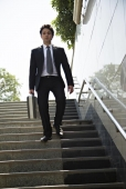 Businessman carrying a briefcase and walking down on stairs of a subway, Connaught Place, New Delhi, India