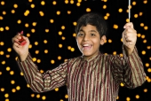 Portrait of a boy holding fire crackers and cheering in front of Diwali decoration