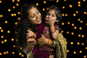 Mother and her daughter holding a diya and smiling in front of Diwali decoration