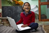 Portrait of a schoolgirl using a laptop on a charpai and laughing