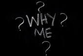 """Why me"" text surrounded with question marks on a blackboard"