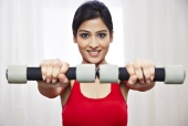 Portrait of a woman exercising with dumbbells and smiling