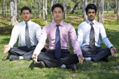 Three young businessmen  meditating in a park