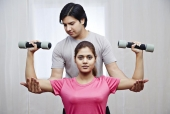 Instructor helping a woman in lifting dumbbells