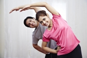 Portrait of a young couple doing stretching exercise and smiling