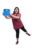 Portrait of a fatty woman holding a weighing scale and cheering