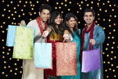 Portrait of four friends showing shopping bags and smiling in front of Diwali decoration
