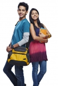 Portrait of a teenage couple carrying bags  and books and smiling