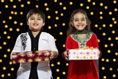 Portrait of a boy and a girl holding gifts and smiling in front of Diwali decoration