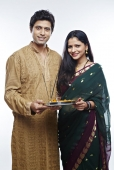 Portrait of a young couple holding a thali of religious offerings and smiling