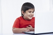 Boy using a laptop and smiling