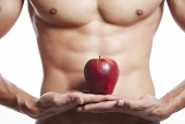 Mid section view of a muscular man holding an apple