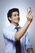 Businessman holding a puzzle cube and smiling
