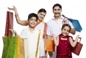 Portrait of a south indian family carrying shopping bags and smiling