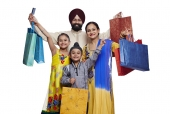 Portrait of a punjabi family carrying shopping bags and smiling