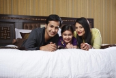 Portrait of a family lying together on the bed and smiling