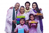 Portrait of a family showing sweets and gifts and cheering during holi festival