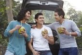 Three friends drinking Coconuts beside a car and smiling