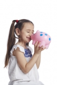 Close-up of a girl playing with a piggy bank and smiling