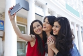 Three female friends taking picture of themselves with a mobile phone in a market