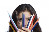 Portrait of a teenage girl showing colour pencils and smiling