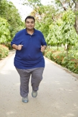 Fatty man jogging in a park and smiling