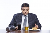 Confused fatty businessman looking at food and drinks in front of him