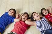Portrait of four children lying together on floor and smiling
