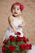 Baby girl standing on the bed with a bouquet of red roses