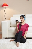 Young woman listening to music with an mp3 player on a couch