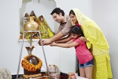 Family pouring water on Shivling in a temple