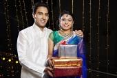 Portrait of a couple holding gifts and smiling in front of Diwali decoration