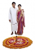 Portrait of a south indian couple standing beside a rangoli and smiling