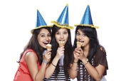 Portrait of three female friends eating ice creams and laughing