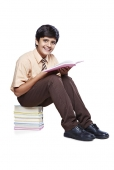 Portrait of a schoolboy reading a book and smiling
