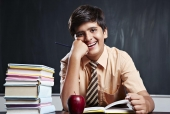 Portrait of a schoolboy studying in a classroom and smiling