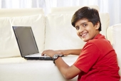 Portrait of a boy using a laptop and smiling