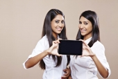 Two female friends showing a digital tablet and smiling
