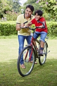 Father teaching his son to ride a bicycle in a park