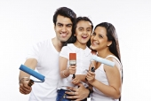 Family holding paint rollers with brush and cheering