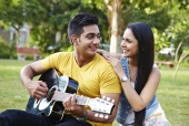 Young man with his girlfriend playing guitar in a park