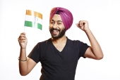 Portrait of a punjabi man holding Indian flag and cheering