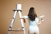 Rear view of a young woman holding a paint roller beside a ladder