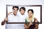 South indian family looking through an empty picture frame and smiling