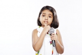 Girl holding a microphone and touching finger on lips