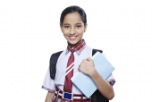 Portrait of a school girl carrying books and smiling