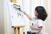 Side profile of a boy painting on canvas